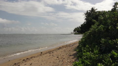 Looking south over the beach in Oahu as gentle waves lap at the shore Stock Footage