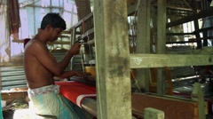Man weaving with a traditional loom in a village in India still shot mid Stock Footage