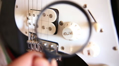 Inspecting Electric Guitar Details Over Magnivying Glass Stock Footage
