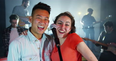 4K Young fun couple sing a duet with backing band at live music event Stock Footage