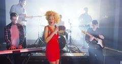 4K Beautiful charismatic female singer performing with band at live music event - stock footage