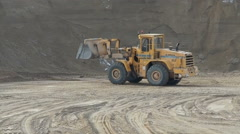 Wheel loader unloading sand at earthmoving works Stock Footage