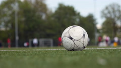 Close football and players in background Stock Footage