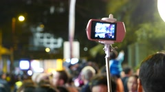 Pink smartphone on the selfie stick, crowded area overhead, night time Stock Footage