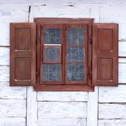 The window of the old wooden log house on the background of wooden walls - stock photo