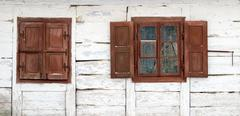 Stock Photo of The window of the old wooden log house on the background of wooden walls