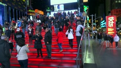 Crowd Tourists on TKTS Red Bleacher Seats at Times Square by night. Stock Footage