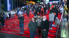 Crowd Tourists on TKTS Red Bleacher Seats at Times Square by night. - stock footage
