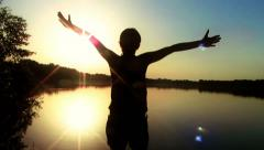 Happy woman with arms outstretched in front of sunset, rear view HD Stock Footage