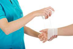 Woman doctor bandaging female hand. Stock Photos