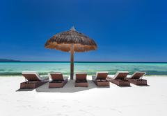 Sun umbrella and beach beds on tropical coastline Stock Photos
