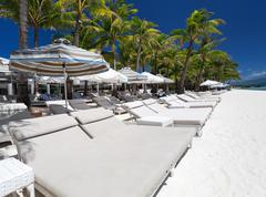 Sun umbrellas and beach beds on tropical coastline - stock photo