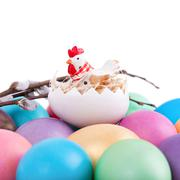 Chicken toy on easter eggs - stock photo