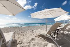 Beach with sun umbrellas and beds - stock photo