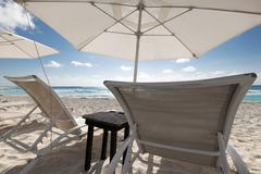 Beach with sun umbrellas and beds Stock Photos