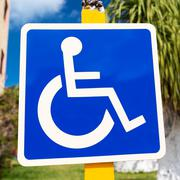 Blue handicapped sign with wheelchair - stock photo