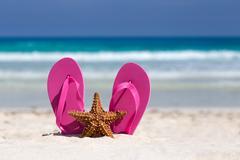 Pink flip flops and starfish on white sandy beach Stock Photos