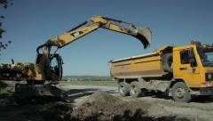 Dredger excavating ground and loading dump truck, roadworks, wide angle view. - stock footage