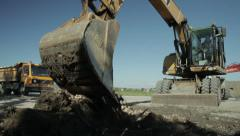 Dredger excavating big root of tree at the road construction, low angle view. - stock footage