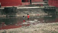 Children play on Bagmati River, Kathmandu, Nepal Stock Footage