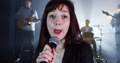 4K Attractive young female singer performing with band at live music event - stock footage