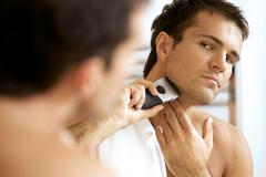 Reflection of young man in mirror shaving with electric shaver Stock Photos