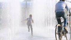 Children playing in the spray of a fountain in a city Park. Stock Footage