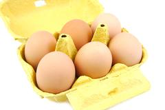 Half a dozen eggs in a yellow carton viewed from the front.  White background - stock photo