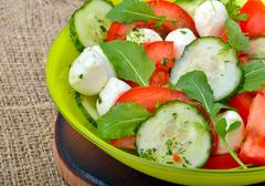 Fresh salad with mozarella cheese, tomatos, cucumber and arugula leaves - stock photo
