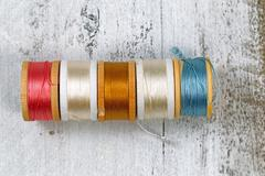 Many colors of thread within their spools - stock photo