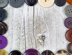 Border of clothing buttons on rustic white wood Stock Photos