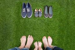 Family legs in jeans and shoes standing  on grass Stock Photos