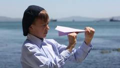 Fascinated boy prepares and launches a paper airplane toy on the beach Stock Footage