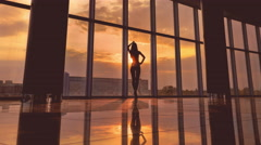 3 in 1 video! The woman stands by sky scraper business center windows by sunset  Stock Footage