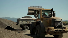 Dump truck loaded with sand leaving, backhoe collect sand, groundwork, roadwork. - stock footage