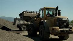 Excavator. Bulldozer charging shovel with sand and loading truck, tracking shot. Stock Footage