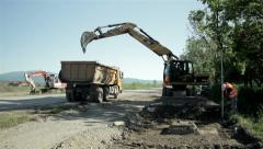 Excavator digging ground and loading tipper, highway reconstruction, wide angle. Stock Footage