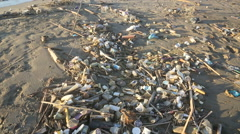 Plastic garbage and other trash covering sandy beach Stock Footage