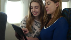 2 women using tablet/IPad for fun and recreation on a plane Stock Footage