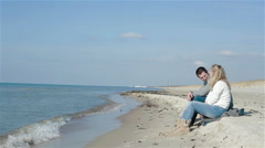 Young couple talking discussing and evaluating something sitting at the beach by Stock Footage