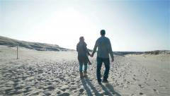 Slow motion of young couple in casual wear walking holding hands in enchanting n Stock Footage