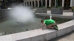 Boy washes in a city fountain in the center of Macao Stock Footage