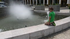 European boy washes in a city fountain in the center of Macao Stock Footage