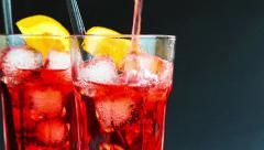 Barman pouring red spritz aperitif aperol cocktail with two orange slices and Stock Footage