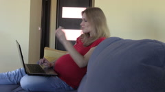 Serious pregnant business woman work with computer at home Stock Footage