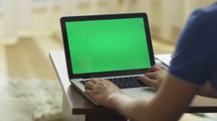 Man Using Laptop with Green Screen in Living Room Stock Footage
