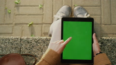 Girl is Using Tablet on Lap Outdoors at Sunny Day Stock Footage