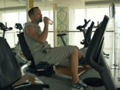 Man drinking water while riding stationary bike in the gym shot at 240 fps NTSC Stock Footage