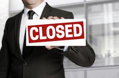 Businessman holding closed sign to viewer - stock photo