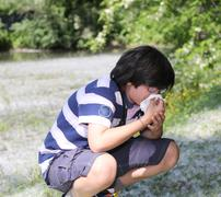 young boy with pollen allergy white handkerchief - stock photo